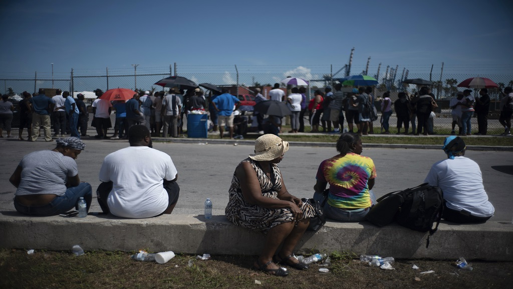 People gather at the port for aid sent by family members and friends in the aftermath of Hurricane Dorian in Freeport, Bahamas, Tuesday, Sept. 10, 2019. Thousands of hurricane survivors are facing the prospect of starting their lives over but with little idea of how or where to even begin. (AP Photo/Ramon Espinosa)