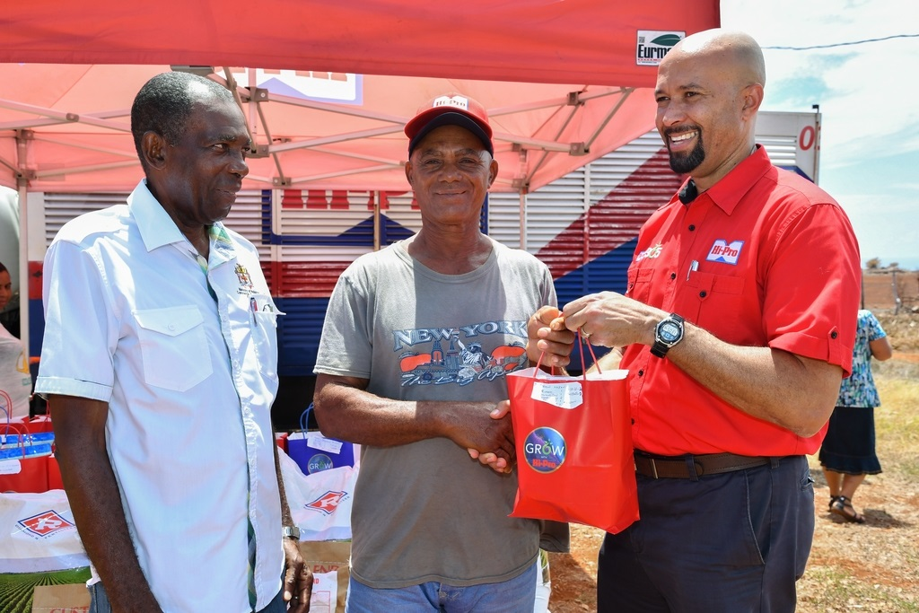 Emanuel Lloyd (centre) Flagaman farmer is presented with one of several Hi-Pro gifts from Col (ret'd) Jaimie Ogilvie (right) Assistant Vice President of Hi-Pro, while JC Hutchinson (left) Minister without Portfolio in the Ministry of Industry, Commerce, Agriculture & Fisheries looks on.