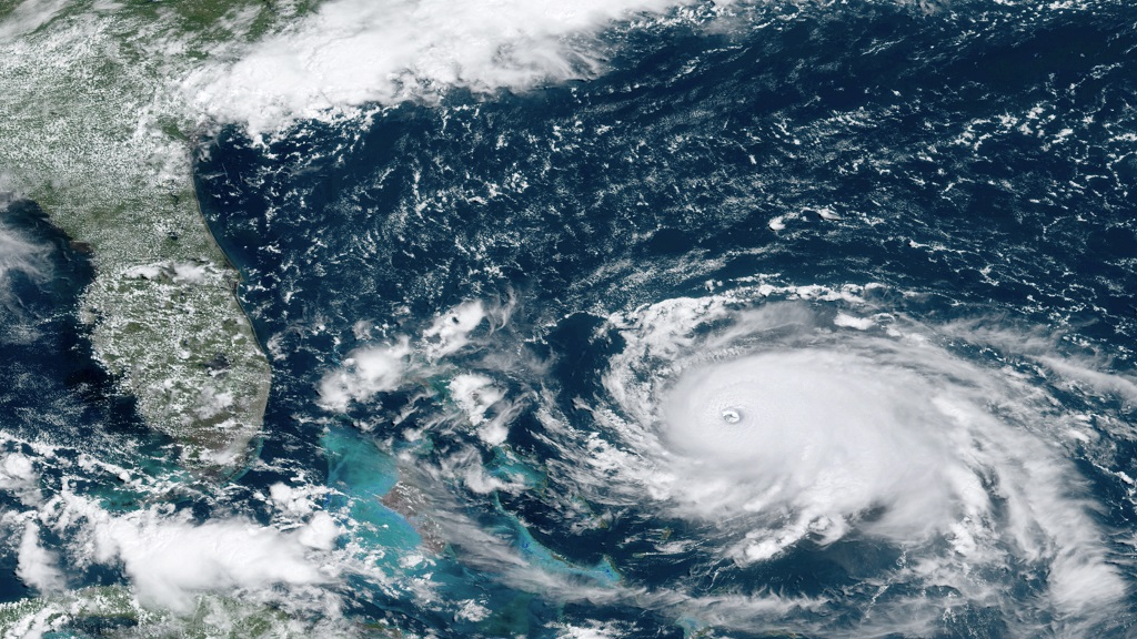 This GOES-16 satellite image taken Saturday, Aug. 31, 2019, at 16:00 UTC and provided by National Oceanic and Atmospheric Administration (NOAA), shows Hurricane Dorian, right, churning over the Atlantic Ocean. Hurricane Dorian bore down on the Bahamas as a fierce Category 4 storm Saturday. (NOAA via AP)