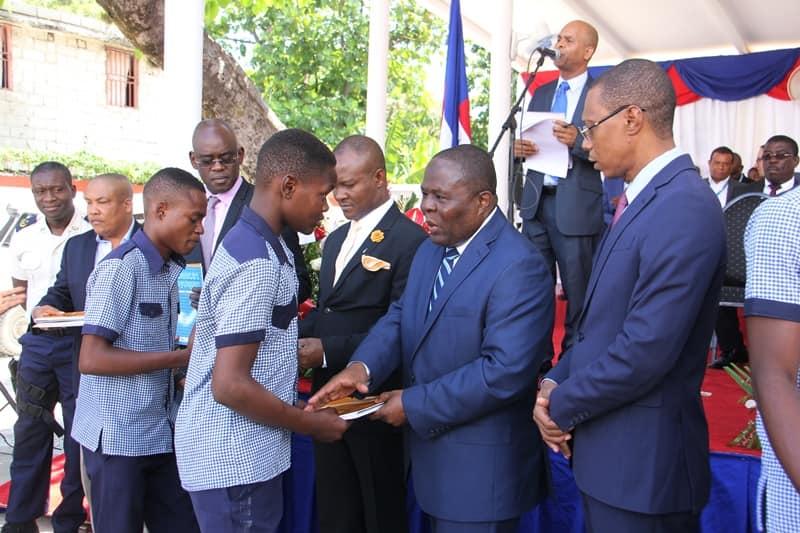 Le ministre de l'Education Nationale, Pierre Josué Agénor Cadet (au milieu) aux côtés du DG du FNE (Joseph Nicolas), distribuant des matériels éducatifs aux élèves de l'Ecole Nationale de Frères./Photo: MENFP.