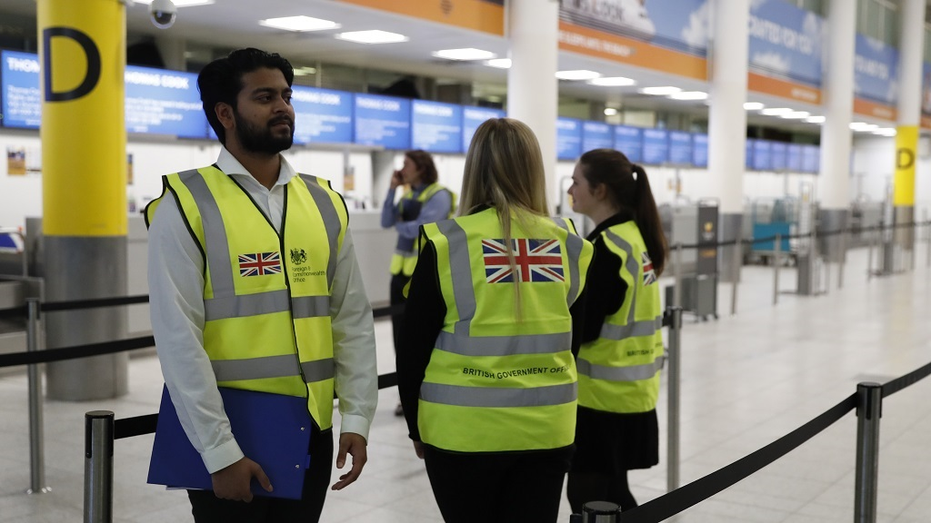 British Foreign Office personnel stand by the entrance to Thomas Cook check-in desks in Gatwick Airport, England Monday, Sept. 23, 2019. British tour company Thomas Cook collapsed early Monday after failing to secure emergency funding, leaving tens of thousands of vacationers stranded abroad. (AP Photo/Alastair Grant)