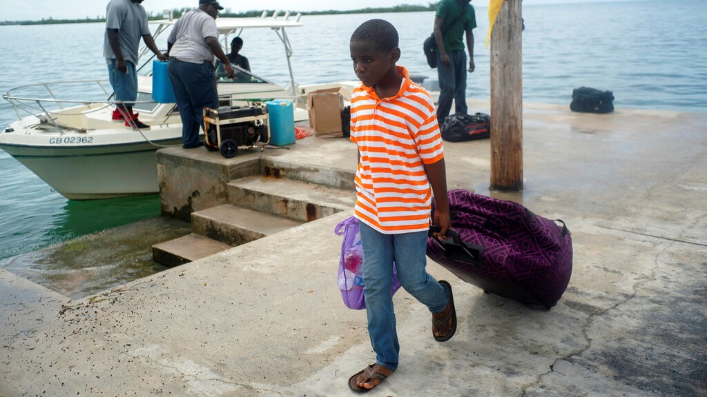 A child evacuated from a nearby Cay due to the danger of floods drags his suitcase when he arrives on a ship at the port before the arrival of Hurricane Dorian in Sweeting's Cay, Grand Bahama, Bahamas, Saturday Aug. 31, 2019. (AP Photo/Ramon Espinosa)