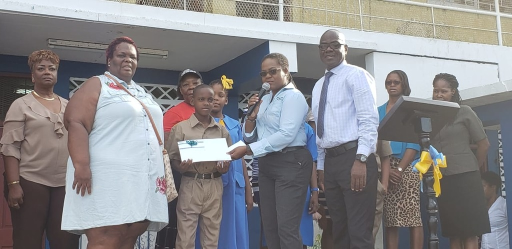 Nicole Scott, Sales Manager at Active Home Centre presented bursary valued at JA$20,000 to Deago Curtis during morning devotion at Dunrobin Primary School. Also in the photo are Noel Watt (right) and Aldene Henry, mother of Deago Curtis, which other members of staff look on.