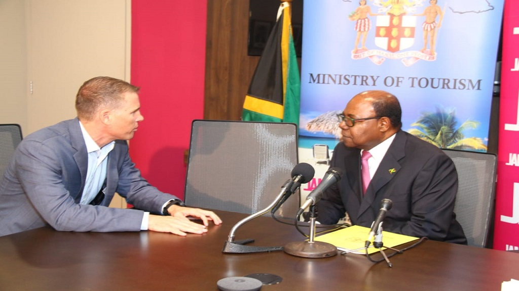 Deputy Chairman of the SRI, Adam Stewart and Tourism Minister, Edmund Bartlett in discussion at the press conference at the Ministry of Tourism in Kingston.