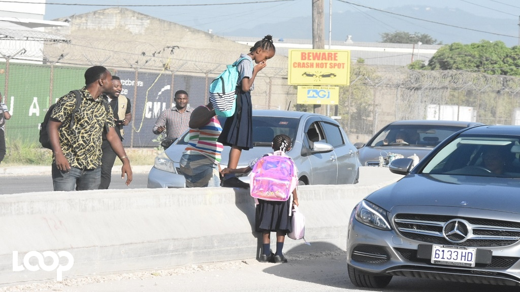 A schoolgirl being assisted over a median along Spanish Town Road in Kingston on Monday, the first day of the new academic year. (PHOTOS: Marlon Reid)