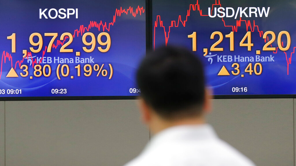 A currency trader walks by the screens showing the Korea Composite Stock Price Index (KOSPI), left, and the foreign exchange rate between U.S. dollar and South Korean won at the foreign exchange dealing room in Seoul, South Korea, Tuesday, Sept. 3, 2019. Asian stock markets were mostly lower Tuesday after investor jitters over U.S.-Chinese trade tension were revived by a report negotiators cannot agree on a schedule for talks this month. (AP Photo/Lee Jin-man)