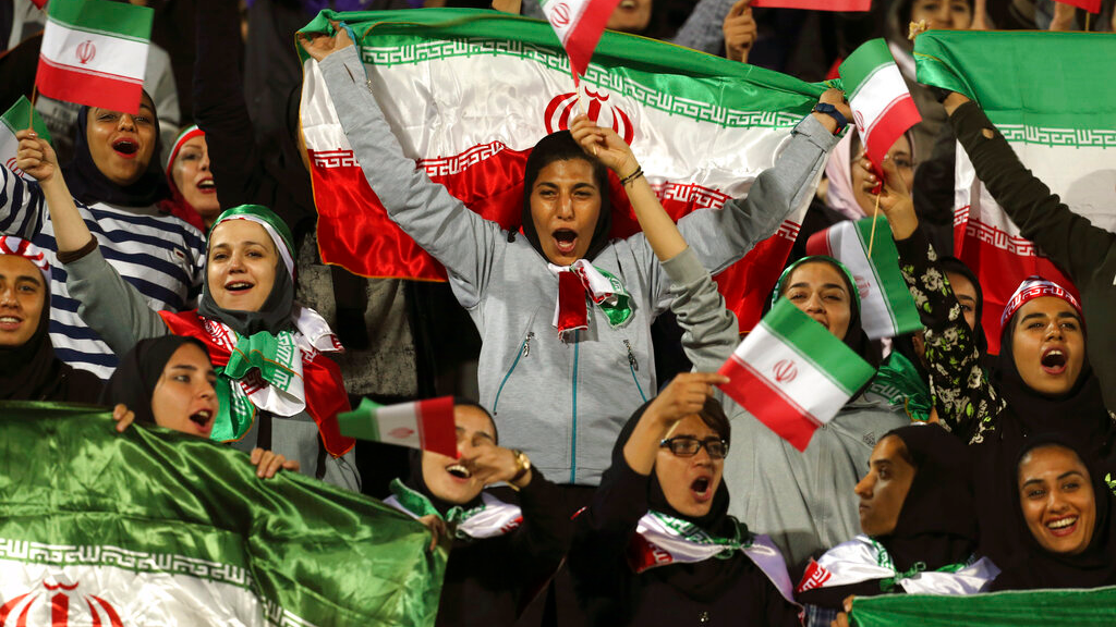 FILE - In this Oct. 16, 2018 file photo, Iranian women cheer as they wave their country's flag after authorities in a rare move allowed a select group of women into Azadi stadium to watch a friendly football match between Iran and Bolivia, in Tehran, Iran. (AP Photo/Vahid Salemi, File)