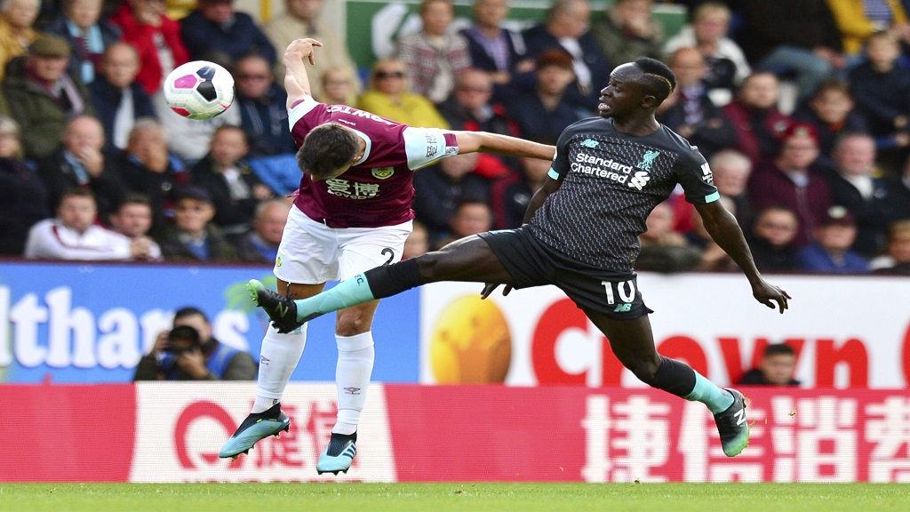 Burnley's Matthew Lowton, left, and Liverpool's Sadio Mane battle for the ball during the English Premier League football match at Turf Moor, Burnley, England, Saturday Aug. 31, 2019. (Anthony Devlin/PA via AP).