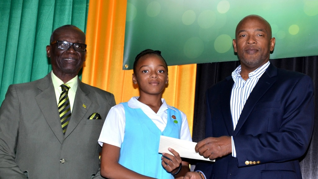 Minister of Local Government and Community Development, Desmond McKenzie (left), looks on as Christopher Seaga, son of late former Prime Minister, Edward Seaga, presents a scholarship award to Wolmer's Girls' student, Lutonya Shelton. Occasion was the launch of the Edward Seaga Scholarship Awards at the Spanish Court Hotel in New Kingston on Wednesday (Photo: JIS).