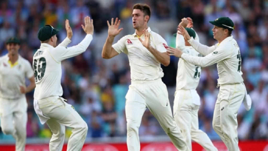 Australia players celebrate the fall of a wicket.