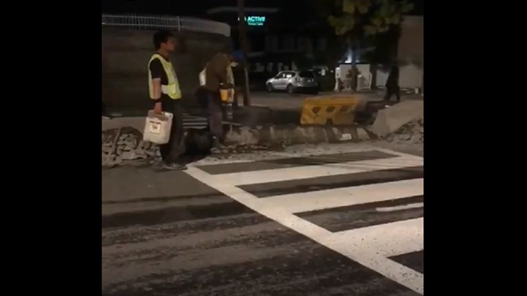 Screengrab of a video showing China Harbour workers removing a section of the concrete median to accommodate pedestrians along Constant Spring Road in St Andrew.