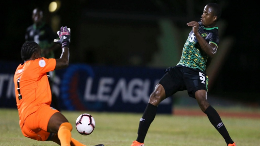 Alvas Powell of Jamaica beats Guyana goalkeeper Akel Clarke during Concacaf Nations League action at the Leonora National Track & Field Center in Leonora, Guyana  on September 9, 2019.