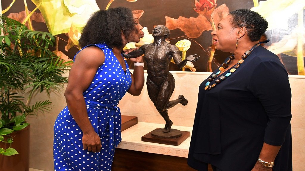 Jamaican Olympian Veronica Campbell Brown reacts after being shown the design of the statue in her honour by the Sport Minister Olivia Grange (right).