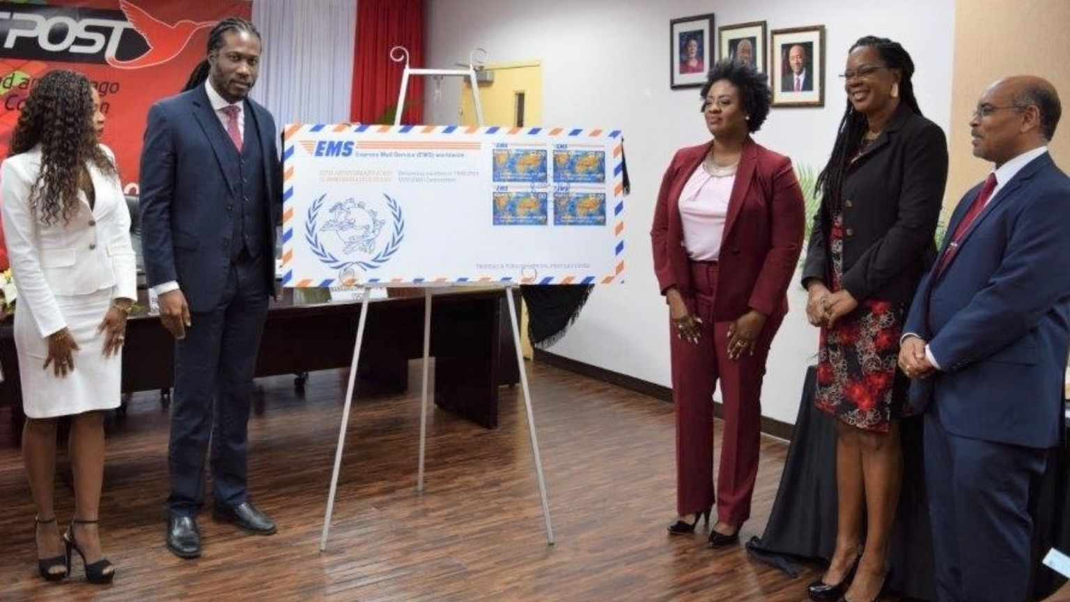 Parliamentary Secretary in the Ministry of Public Utilities , Adrian Leonce (centre, left),  unveils the commemorative stamp at yesterday's launch. Looking on are Natasha Phillips, Director of the Board of TTPost (left), Averline Scott, Postal Sector Specialist in MPU (centre, right), Arlene Johnson Lawrence, Programme Manager of Sectorial Programmes and Projects Unit in MPU and George Alexis, Managing Director (Ag.) of TTPost.