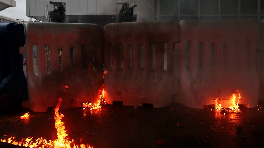 Exploded tear gas shells, thrown back by protestors, stand in flames by a police barricade in central Hong Kong, Saturday, Aug. 31, 2019. (AP Photo/Jae C. Hong)