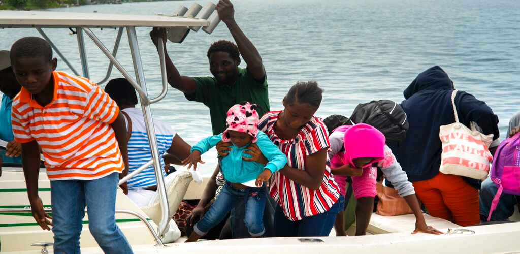 A woman carries a girl in her arms after being evacuated from a nearby Cay due to the danger of floods after arrive on a ship at the port before the arrival of Hurricane Dorian in Sweeting's Cay, Grand Bahama, Bahamas, Saturday Aug. 31, 2019.