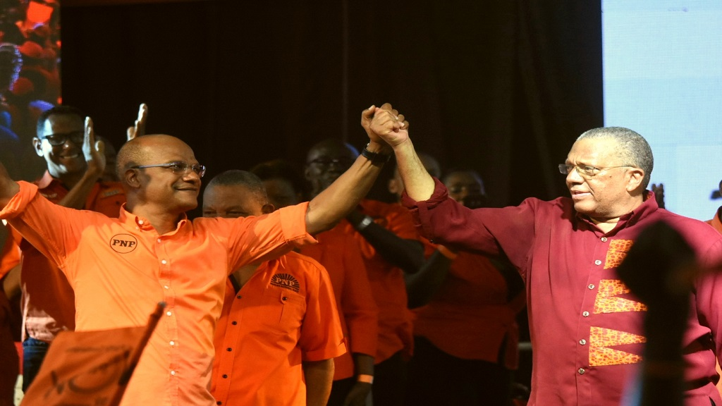 Peter Bunting (left) and his party leader and President, Dr Peter Phillips, in a show of unity at the People's National Party's (PNP) annual conference at the National Arena on Sunday. (Photos: Marlon Reid)