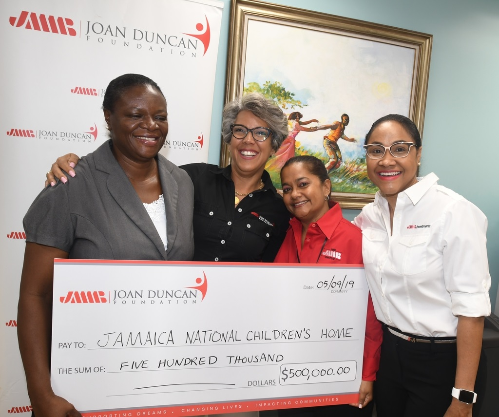 From second left: Kim Mair, CEO, JMMB Joan Duncan Foundation, Carolyn DaCosta, group chief compliance manager and Fornia Young, general manager, investments client partnership are indeed a picture of cheerful givers, as they make a donation on behalf the company and its clients to Nadeen Waugh (left), director of Jamaica National Children's Home.