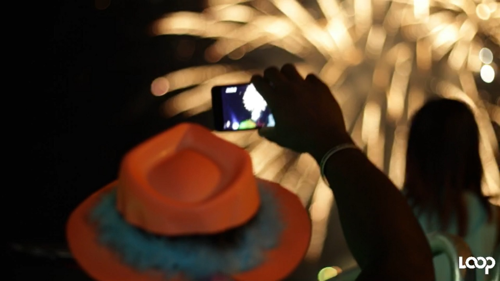 A man uses his phone to record the fireworks display at the annual UDC 'Fireworks on the Waterfront' show on New Year's Eve.