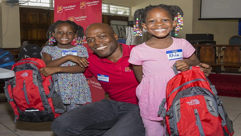 Lancelot Leslie (centre), Chief Financial Officer, CIBC FirstCaribbean with some of the beneficiaries of the backpack presentation and treat hosted by the bank with the Salvation Army for students of five inner-city communities.