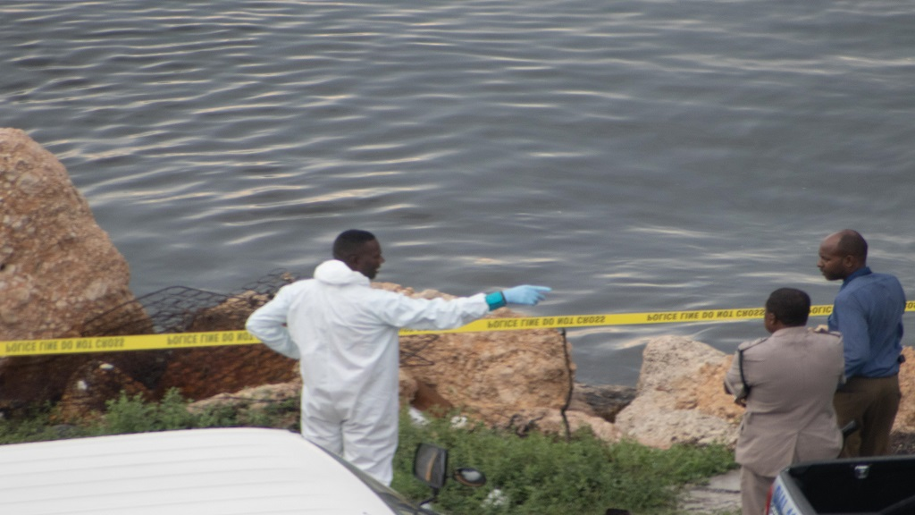 A scene of crime investigator directs activities where a body was found along the Kingston waterfront on Wednesday afternoon. (Photos: Shawn Barnes)