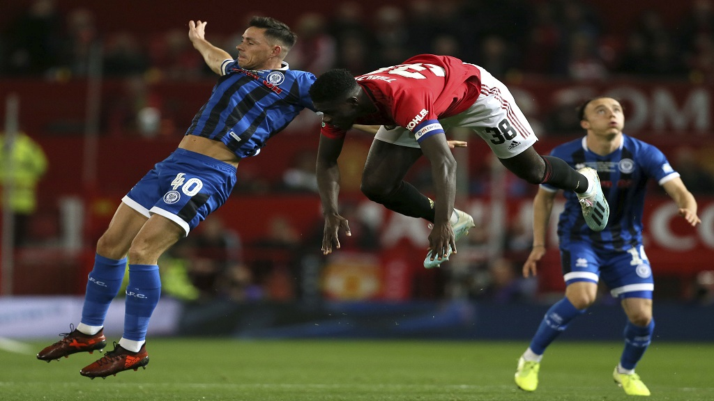 Rochdale's Ian Henderson, left, and Manchester United's Axel Tuanzebe battle for the ball during their English League Cup, Third Round football match at Old Trafford, Manchester, England, Wednesday, Sept. 25, 2019. (Richard Sellers/PA via AP).