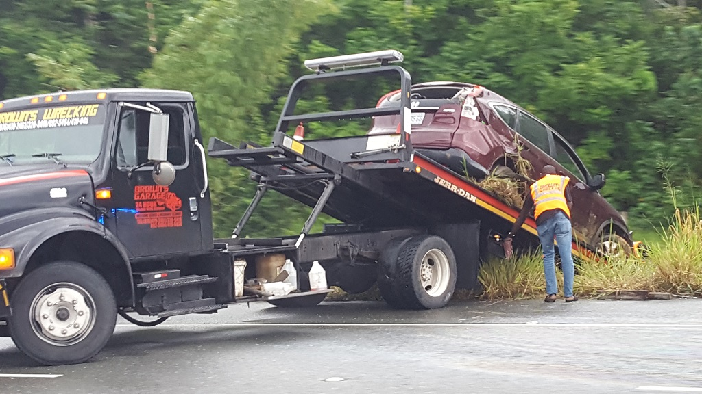A wrecker had to lift a Honda CRV out of bushes following a traffic accident along the North South Highway on Wednesday afternoon. (Photo: Marlon Reid)