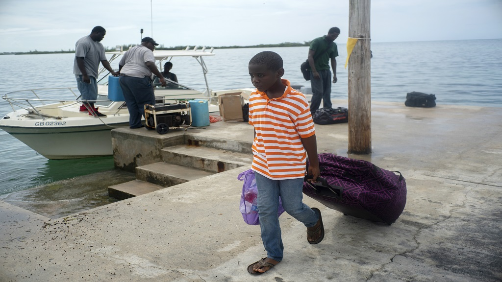 A child evacuated from a nearby Cay due to the danger of floods drags his suitcase when he arrives on a ship at the port before the arrival of Hurricane Dorian in Sweeting's Cay, Grand Bahama, Bahamas, Saturday August 31, 2019. (AP Photo/Ramon Espinosa)