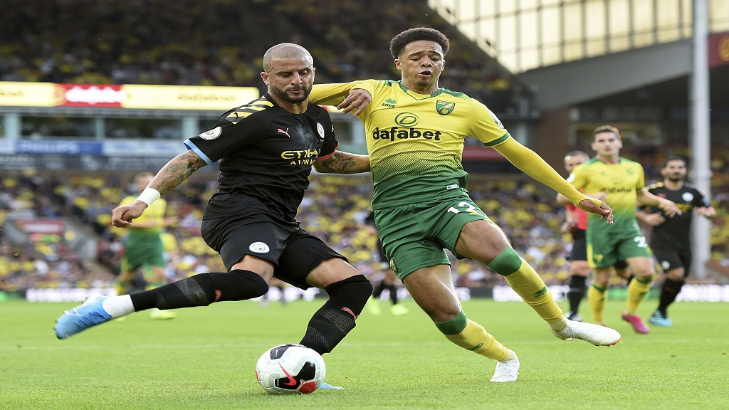 Manchester City's Kyle Walker, left, and Norwich City's Jamal Lewis battle for the ball during first half action of the English Premier League football match at Carrow Road, Norwich, England, Saturday, Sept. 14, 2019. (Joe Giddens/PA via AP)