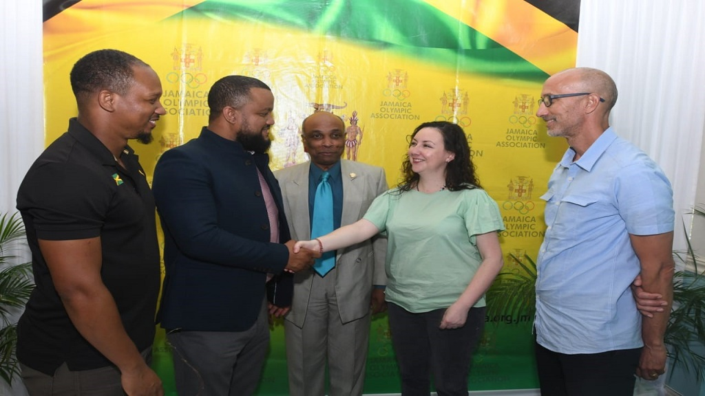 JOA General Secretary and CEO, Ryan Foster (second left), shakes hands with Gisselle Burbano (second right), UNESCO representative, Caribbean Cluster, following the signing of a MOU between both parties at Olympic Manor, the JOA's headquarters on Cunningham Avenue in Kingston. Looking on are JOA Board members Michael Frater, President Christopher Samuda and Alan Beckford.