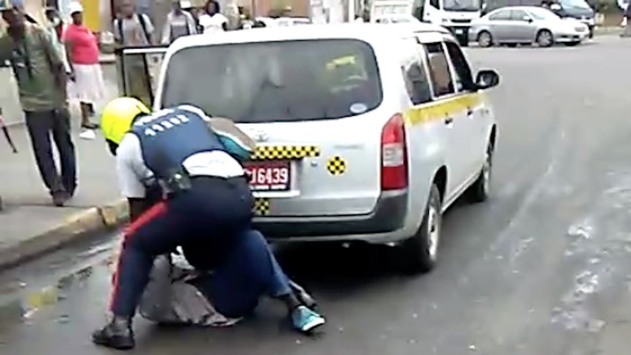 Screen grab shows a policeman attempting to restrain a taxi driver.