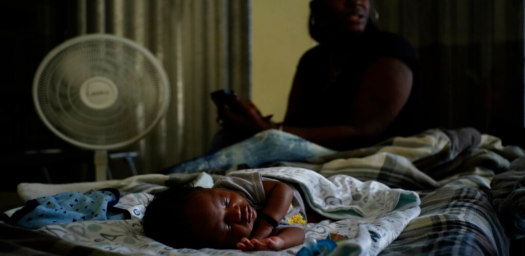 A baby sleeps inside a church that was opened up as a shelter for residents who will wait out Hurricane Dorian in Freeport on Grand Bahama, Bahamas, Sunday, Sept. 1, 2019.