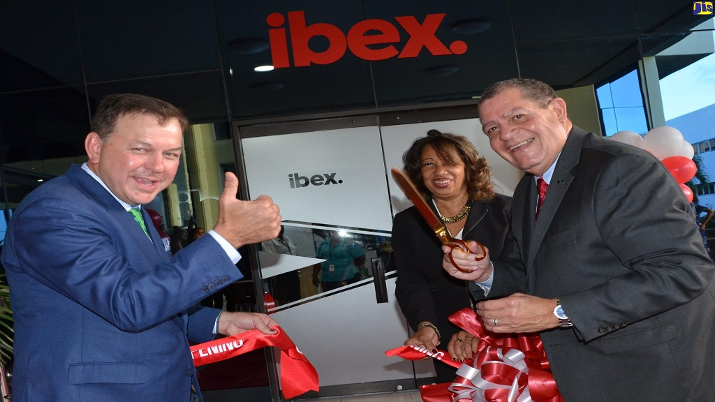 Industry, Commerce, Agriculture and Fisheries Minister, Audley Shaw (right), cuts the ribbon to officially open ibex's third location in Jamaica at the Courtleigh building in New Kingston on September 4. Others pictured (from left) are Chief Executive Officer of ibex, Bob Dechant, and Jamaica Promotions Corporation (JAMPRO) President, Diane Edwards.