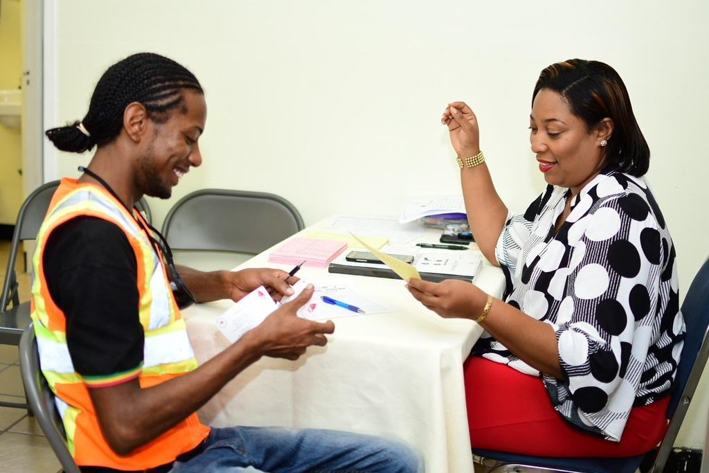 Keishawna Pinnock (right), assistant blood donor organizer, NBTS, registers first time blood donor Shawn Budram (left) at the Red Stripe blood drive.