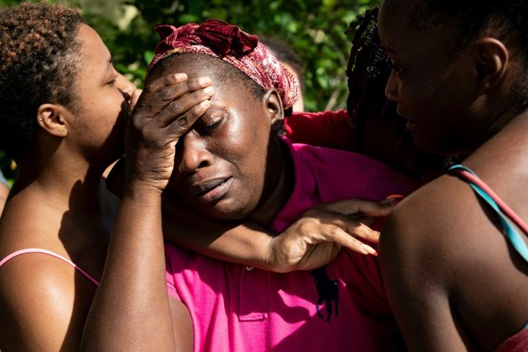 AFP / Brendan SmialowskiCatherine Russel est reconfortée par des proches à son arrivée à l'aéroport de Nassau en provenance d'Abaco Island, durement touchée par l'ouragan Dorian, le 4 septembre 2019 à Nassau.