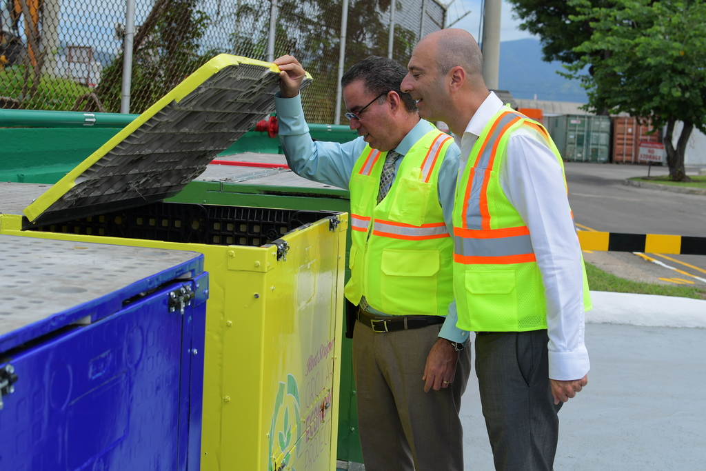 Daryl Vaz (left), the minister responsible for land, environment, climate change and investment and Red Stripe Managing Director Luis Prata examine a recycling bin at Red Stripe.