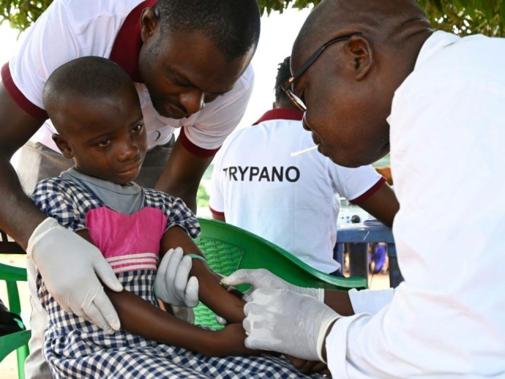 Une équipe médicale prélève un échantillon de sang à un fillette pour dépister la maladie du sommeil, à Paabénéfla, en Côte d'Ivoire, le 11 octobre 2019  AFP - ISSOUF SANOGO