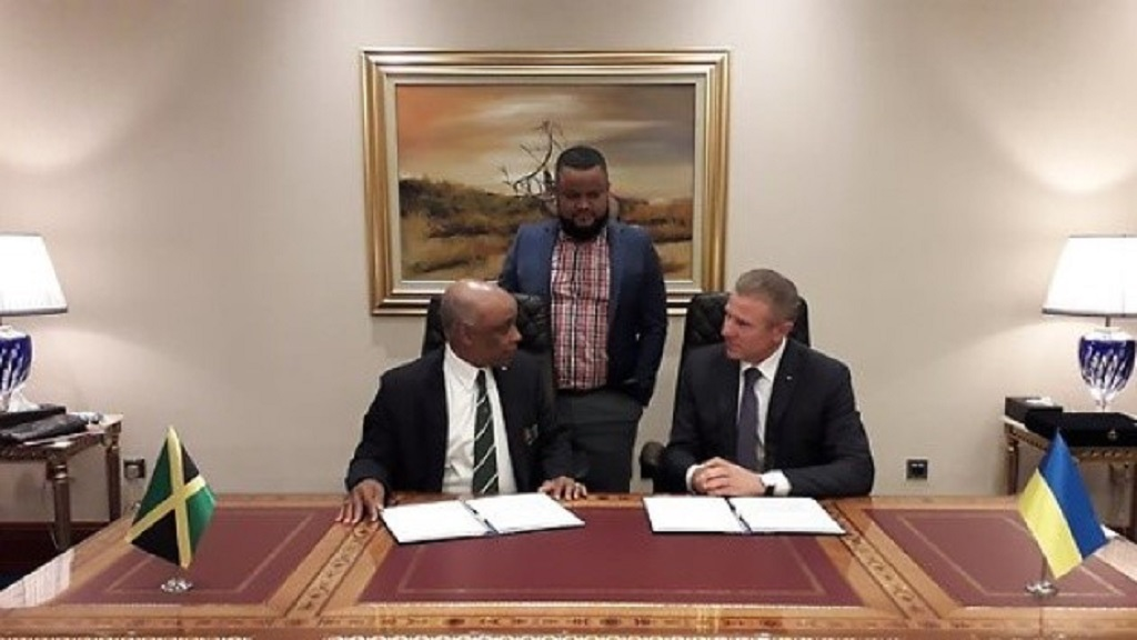 Jamaica Olympic Association (JOA) President, Christopher Samuda (left) and Sergey Bubka (right), President, Ukraine Olympic Committee, sign a Memorandum of Understanding (MOU) in Doha, Qatar recently. Looking on is Ryan Foster, the JOA's CEO/General Secretary.