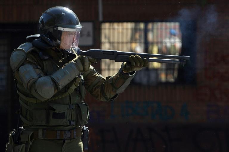 Un policier face aux manifestants à Santiago le 24 octobre 2019