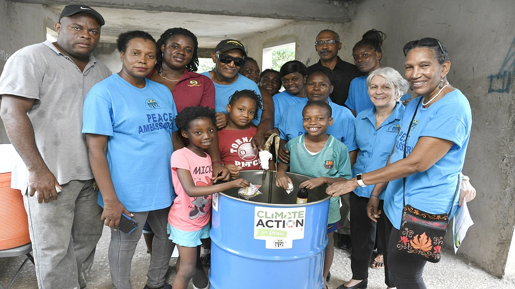 Members of the Violence Prevention Alliance (VPA)  present drums to the community of Cassava Piece in St Andrew as part of their  International Peace Day activities recently. Some 21 drums were donated to the community to assist with  waste disposal in the community.
