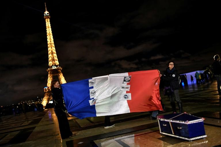 """Des """"policiers en colère"""" tiennent le drapeau français et posent près d'un cercueil représentant les fonctionnaires de police décédés, Esplanade du Trocadéro à Paris, 12 mars 2019"""