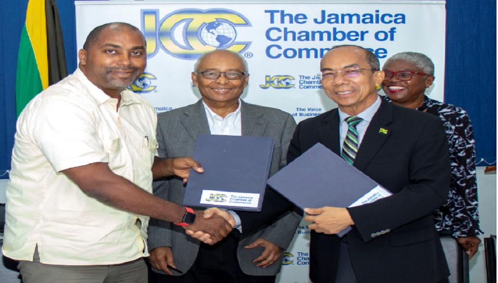 Julian Robinson, General Secretary of the PNP and Dr. Horace Chang, General Secretary of the JLP share a handshake after signing the Jamaica Debates Commission (JDC) MOU to participate in upcoming General Elections national political debates. Looking on are Noel daCosta, JDC Chairman and Jeniffer Grant, JDC Commissioner