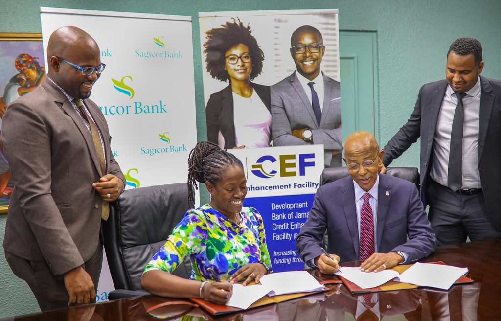 Sagicor Bank CEO Chorvelle Johnson Cunningham (second left) and Development Bank of Jamaica (DBJ) Managing Director Milverton Reynolds (third left) sign their respective copies of a new partnership agreement between the two entities for DBJ's redesigned Credit Enhancement Facility. Looking on are Sagicor Bank Head of SME Banking Howard Smith (left) and DBJ Project Coordinator for the Access to Finance Project Hugh Grant (right).