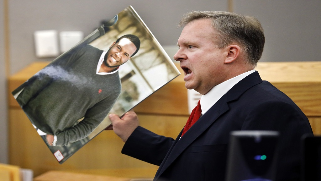 Assistant District Attorney Jason Hermus waves a photo of Botham Jean at the jury as he presents his closing arguments in Amber Guyger's murder trial in the 204th District Court at the Frank Crowley Courts Building in Dallas, Monday, September 30, 2019. (Tom Fox/The Dallas Morning News via AP, Pool)