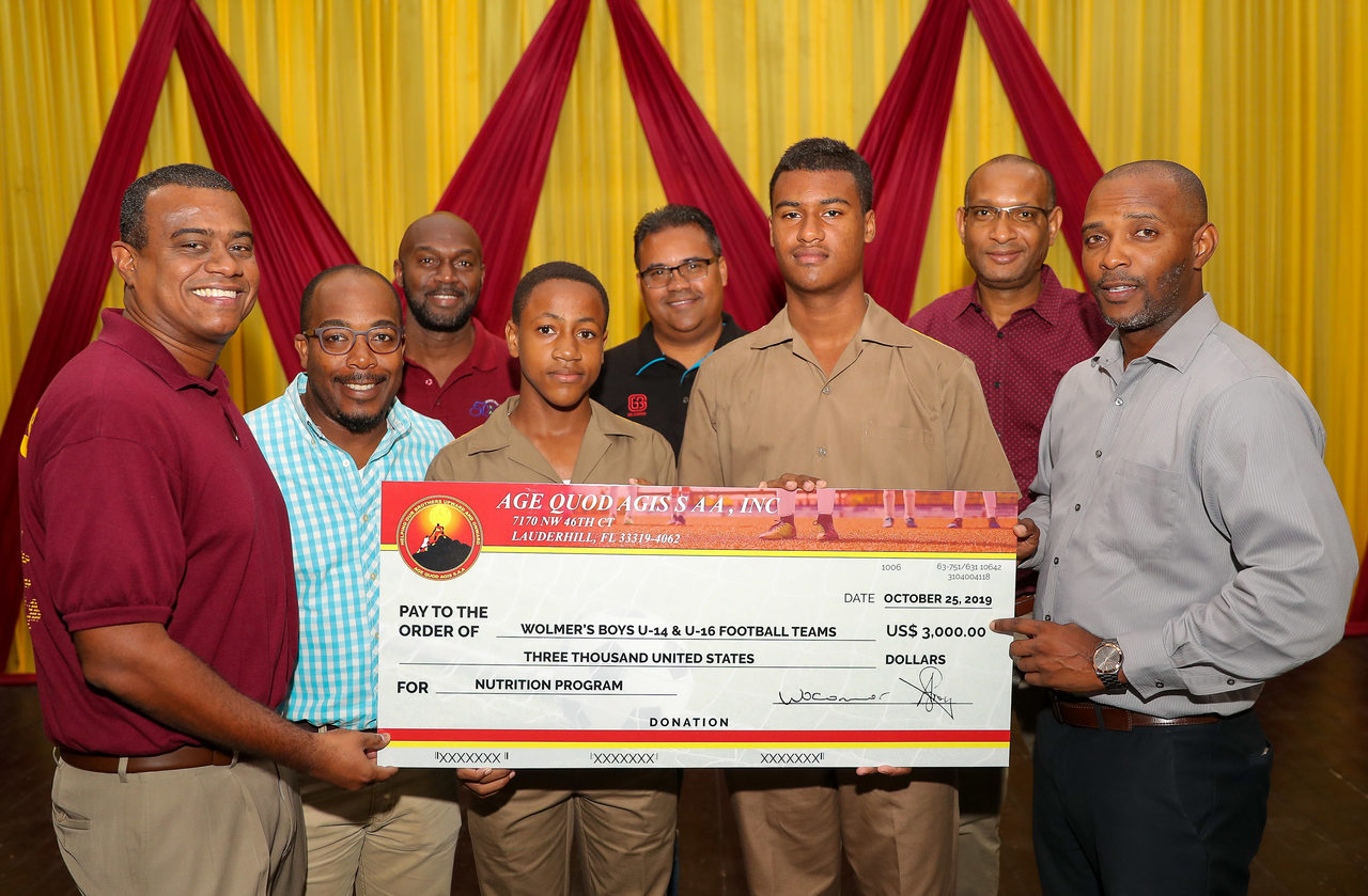 Members of the Wolmer's Boys School under-14 and under-16 football teams pose with the symbolic cheque of US$3,000 from Wolmer's old boys from the Age Quod Agis Sports Alumni Association (SAA).