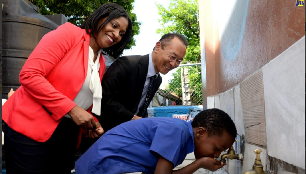Director, Donor and Partnership Management, National Education Trust (NET), Latoya Harris (left); and Deputy Head of Mission, Embassy of Japan, Shotoku Habukawa (right), observe as a student of the Iris Gelly Primary School, Jordaine Beckford, drinks water from a pipe, at the official handover of a water harvesting system at the school, in Kingston,