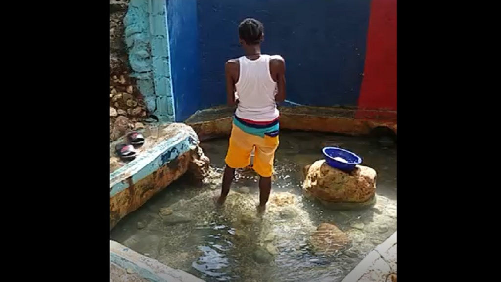 A man prepares a meal in the 'firewater' in St Ann.