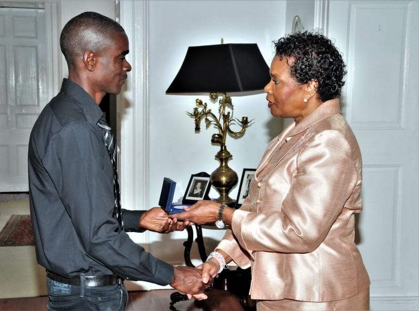 Governor General, Dame Sandra Mason presents National Conservation Commission (NCC) Lifeguard, Terrence Hinds with the Mountbatten Medal at Government House today. (B.Hinds/BGIS)