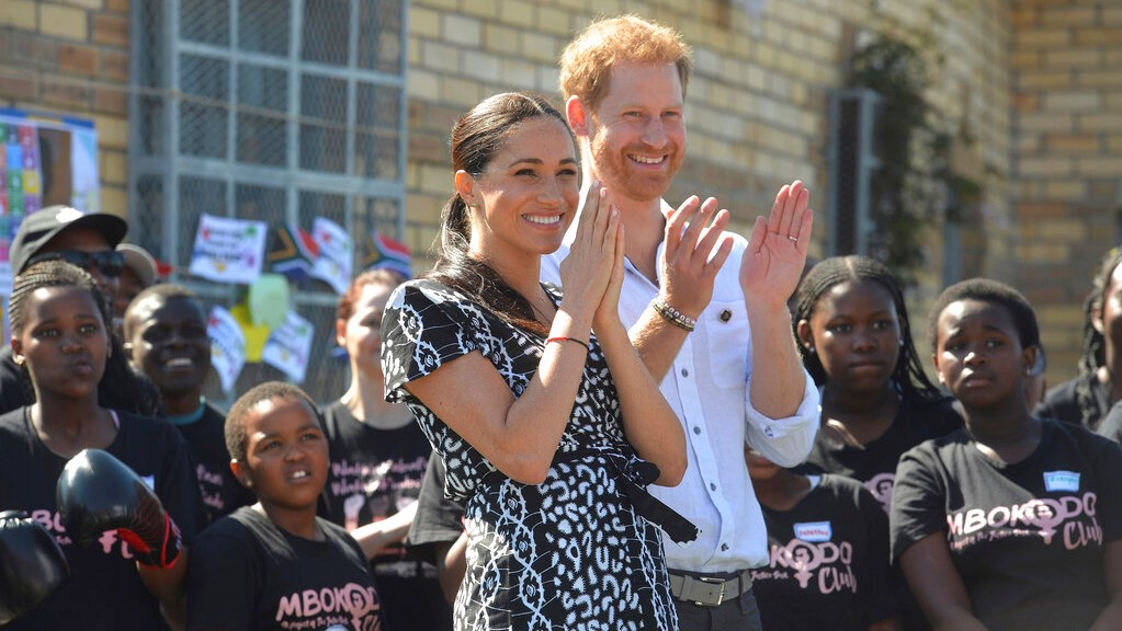 In this Monday, Sept, 23, 2019 file photo, Britain's Prince Harry and Meghan, Duchess of Sussex greet youths on a visit to the Nyanga Methodist Church in Cape Town, South Africa. (Courtney Africa/Pool via AP, File)