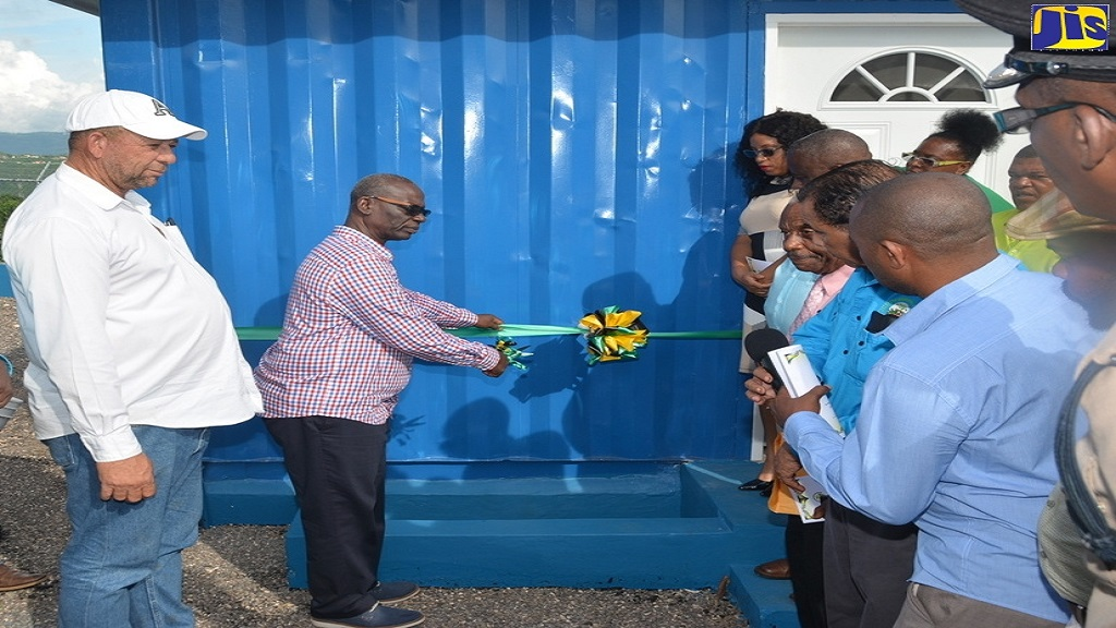 Minister of Local Government and Community Development, Desmond McKenzie (second left), cuts the ribbon to mark the official opening of the Top Hill Water Shop in St Elizabeth on Thursday, October 3. Sharing in the moment are Deputy Mayor of Black River, Albert Williams (left), and other stakeholders.
